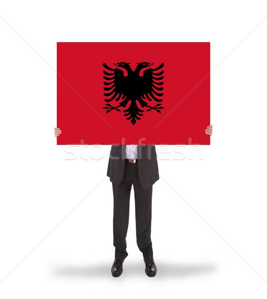Businessman holding a big card, flag of Albania Stock photo © michaklootwijk