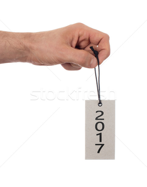 Hand holding a tag - New year - 2017 Stock photo © michaklootwijk