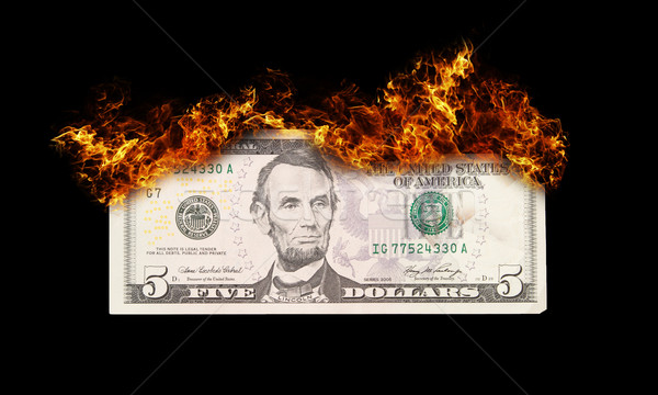Burning five dollar bill symbolizing careless money management Stock photo © michaklootwijk