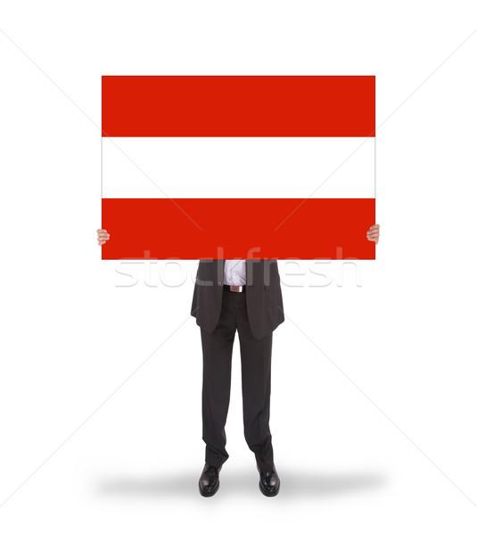 Smiling businessman holding a big card, flag of Austria Stock photo © michaklootwijk