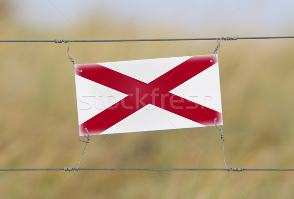Border fence - Old plastic sign with a flag Stock photo © michaklootwijk
