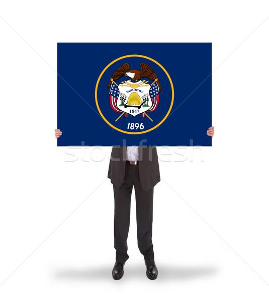 Smiling businessman holding a big card, flag of Utah Stock photo © michaklootwijk