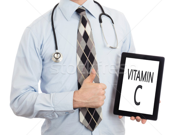 Doctor holding tablet - Vitamin C Stock photo © michaklootwijk