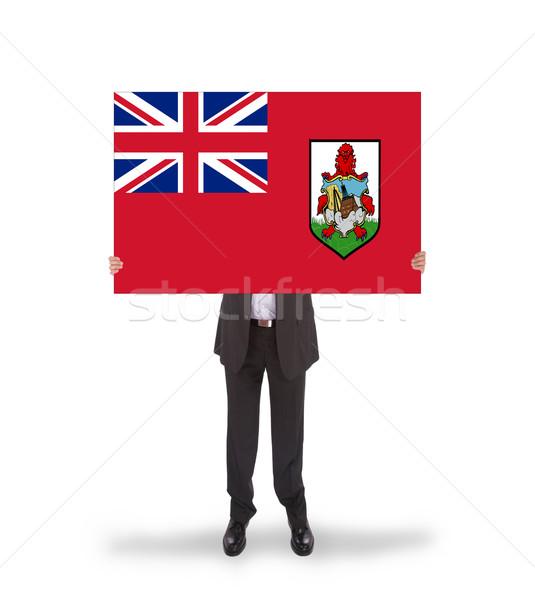 Smiling businessman holding a big card, flag of Bermuda Stock photo © michaklootwijk
