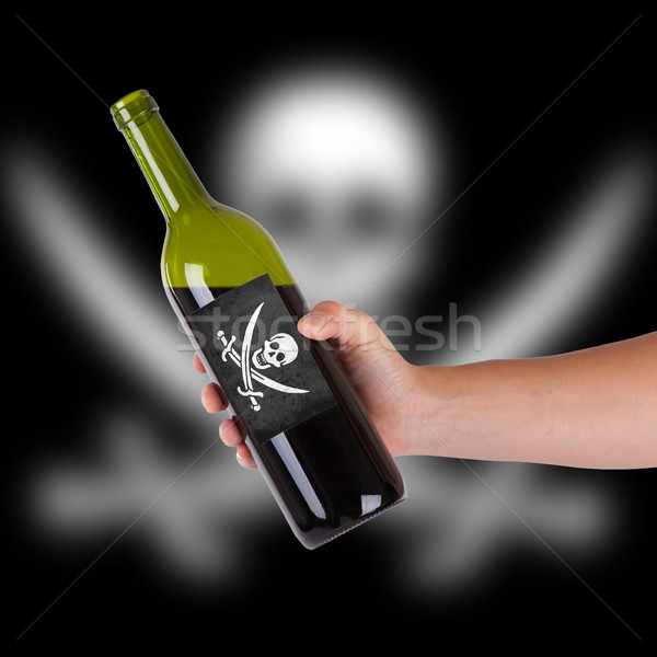 Stock photo: Hand holding a bottle of red wine