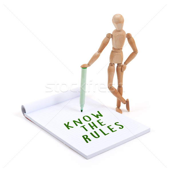 Wooden mannequin writing in scrapbook - Know the rules Stock photo © michaklootwijk
