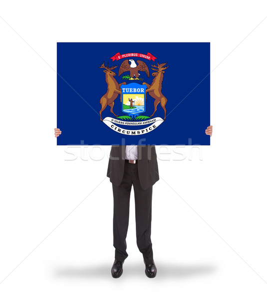 Smiling businessman holding a big card, flag of Michigan Stock photo © michaklootwijk