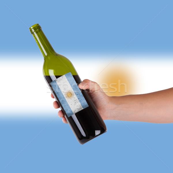 Kéz tart üveg vörösbor címke Argentína Stock fotó © michaklootwijk