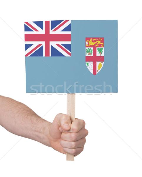 Kéz tart kicsi kártya zászló Fidzsi-szigetek Stock fotó © michaklootwijk