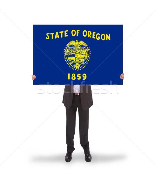 Smiling businessman holding a big card, flag of Oregon Stock photo © michaklootwijk