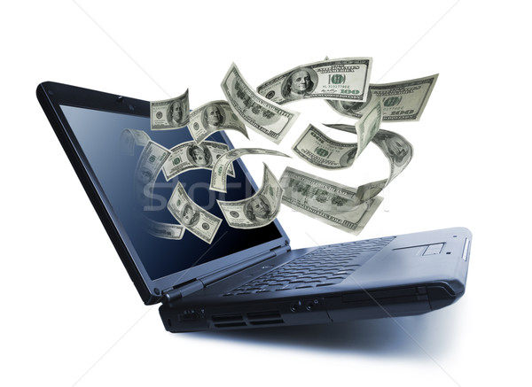 Stock photo: Money pouring out from a notebook computer