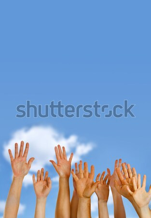 Hands raised up in air across blue sky  Stock photo © mikdam