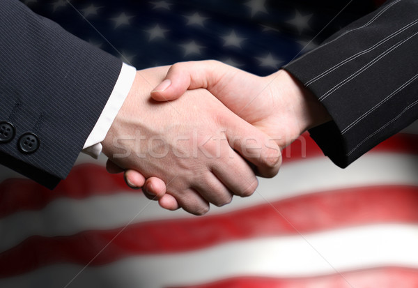 hand shake and a American flag in the background Stock photo © mikdam