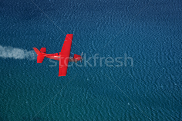 small red airplane flies over a sea Stock photo © mike_kiev