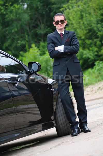 The young man with glasses and suit stand near to expensive car Stock photo © mikhail_ulyannik