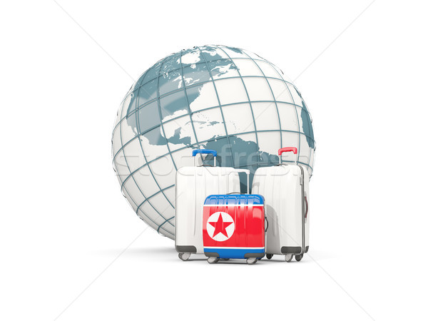 Luggage with flag of korea north. Three bags in front of globe Stock photo © MikhailMishchenko
