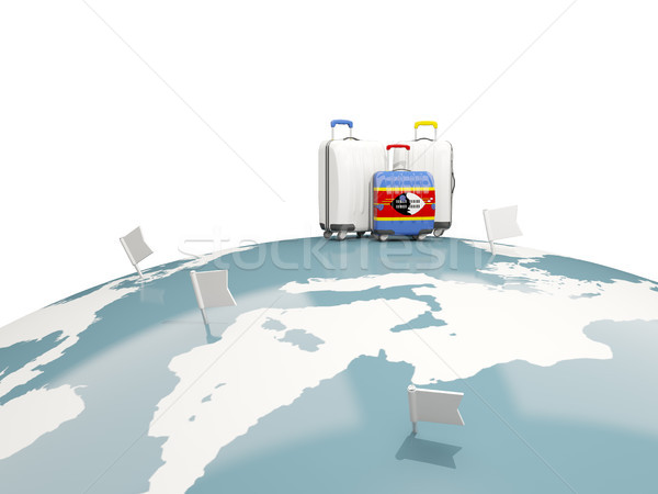 Luggage with flag of swaziland. Three bags on top of globe Stock photo © MikhailMishchenko