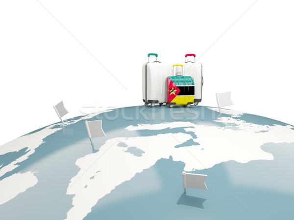 Luggage with flag of mozambique. Three bags on top of globe Stock photo © MikhailMishchenko