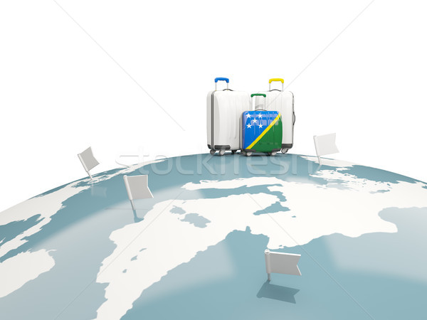 Luggage with flag of solomon islands. Three bags on top of globe Stock photo © MikhailMishchenko