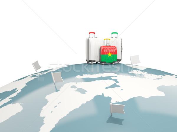 Luggage with flag of burkina faso. Three bags on top of globe Stock photo © MikhailMishchenko