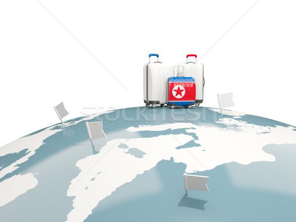 Luggage with flag of korea north. Three bags on top of globe Stock photo © MikhailMishchenko