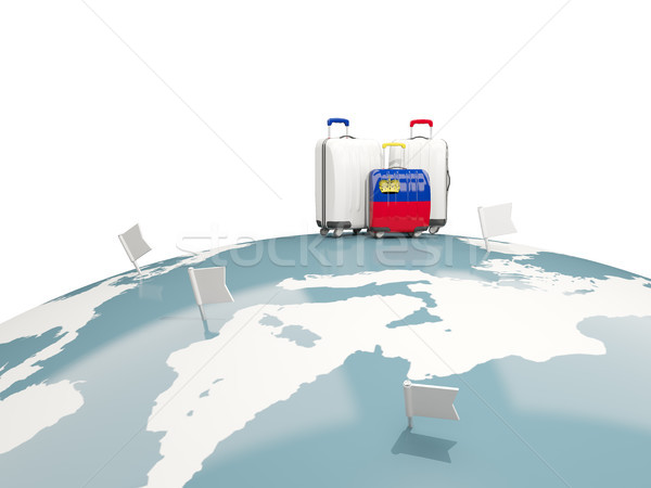 Luggage with flag of liechtenstein. Three bags on top of globe Stock photo © MikhailMishchenko