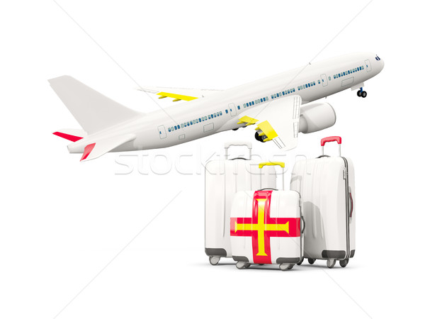 Luggage with flag of guernsey. Three bags with airplane Stock photo © MikhailMishchenko