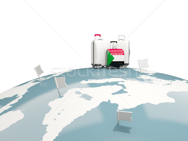 Luggage with flag of sudan. Three bags on top of globe Stock photo © MikhailMishchenko