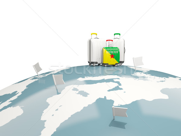 Luggage with flag of french guiana. Three bags on top of globe Stock photo © MikhailMishchenko