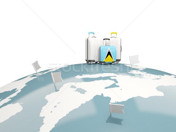 Luggage with flag of saint lucia. Three bags on top of globe Stock photo © MikhailMishchenko