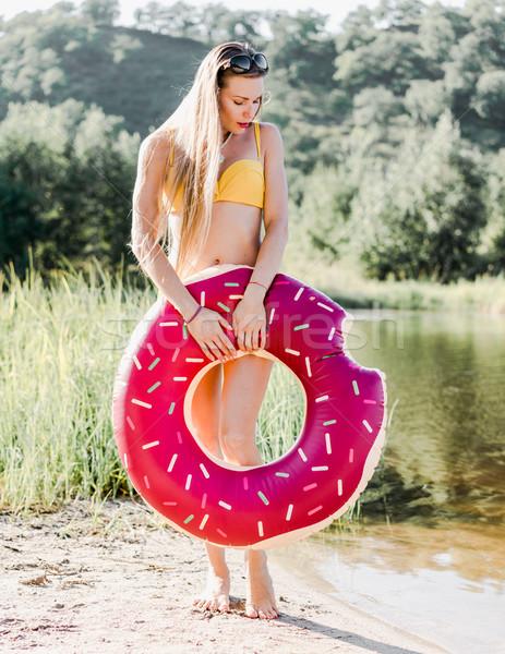 Femme jaune bikini gonflable matelas lac Photo stock © MikhailMishchenko