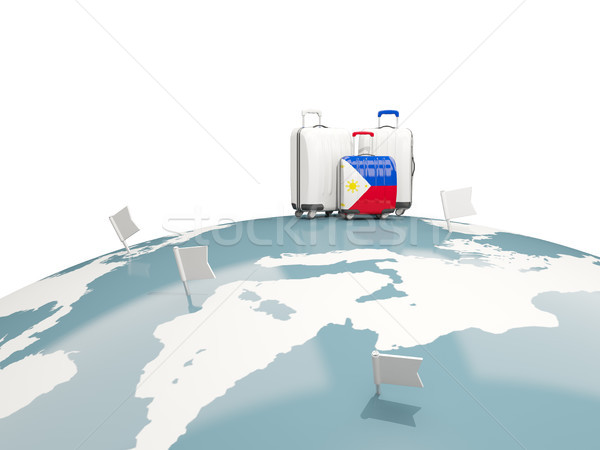 Luggage with flag of philippines. Three bags on top of globe Stock photo © MikhailMishchenko