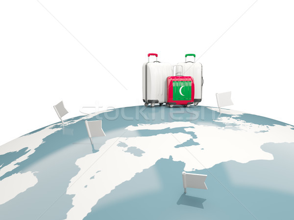 Luggage with flag of maldives. Three bags on top of globe Stock photo © MikhailMishchenko