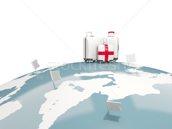 Luggage with flag of england. Three bags on top of globe Stock photo © MikhailMishchenko