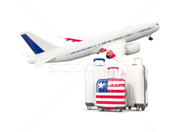 Luggage with flag of liberia. Three bags with airplane Stock photo © MikhailMishchenko