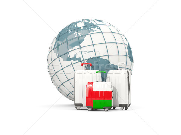 Luggage with flag of oman. Three bags in front of globe Stock photo © MikhailMishchenko