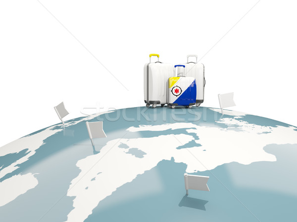 Luggage with flag of bonaire. Three bags on top of globe Stock photo © MikhailMishchenko