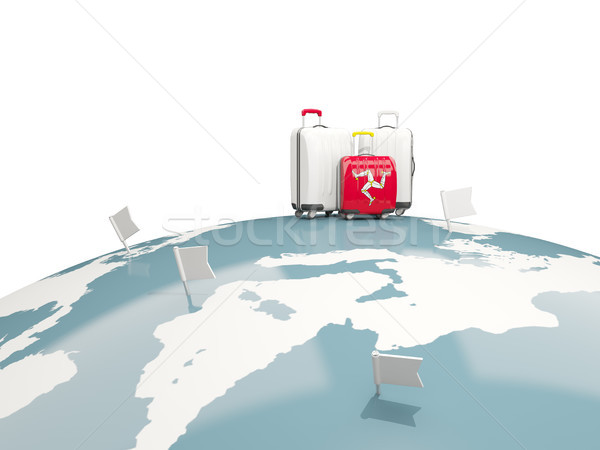 Luggage with flag of isle of man. Three bags on top of globe Stock photo © MikhailMishchenko