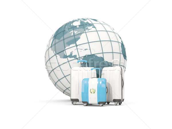 Luggage with flag of guatemala. Three bags in front of globe Stock photo © MikhailMishchenko