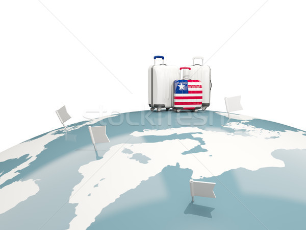 Luggage with flag of liberia. Three bags on top of globe Stock photo © MikhailMishchenko