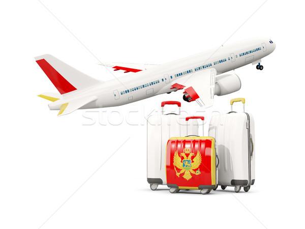 Luggage with flag of montenegro. Three bags with airplane Stock photo © MikhailMishchenko
