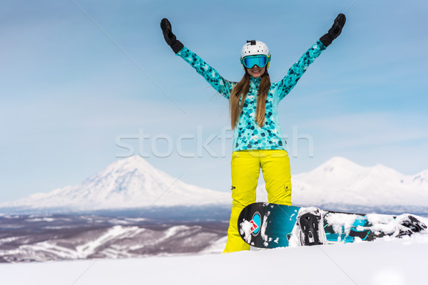 Stock photo: Happy young woman with snowboard in front of volcanos
