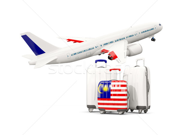 Luggage with flag of malaysia. Three bags with airplane Stock photo © MikhailMishchenko