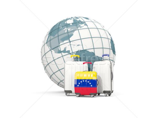Luggage with flag of venezuela. Three bags in front of globe Stock photo © MikhailMishchenko