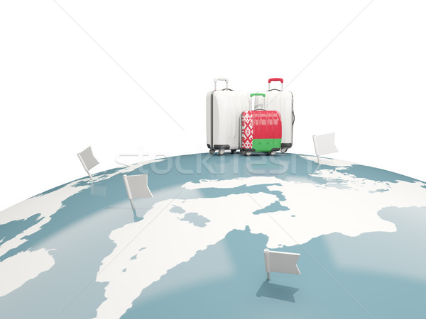 Luggage with flag of belarus. Three bags on top of globe Stock photo © MikhailMishchenko