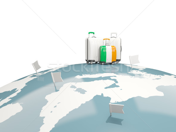 Luggage with flag of ireland. Three bags on top of globe Stock photo © MikhailMishchenko