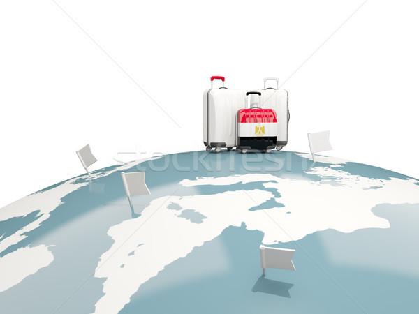 Luggage with flag of egypt. Three bags on top of globe Stock photo © MikhailMishchenko