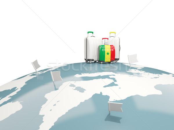 Luggage with flag of senegal. Three bags on top of globe Stock photo © MikhailMishchenko