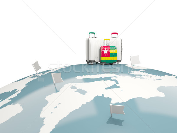 Luggage with flag of togo. Three bags on top of globe Stock photo © MikhailMishchenko