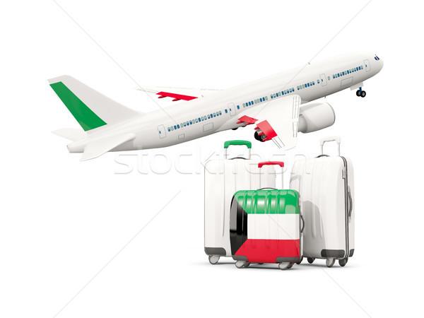 Luggage with flag of kuwait. Three bags with airplane Stock photo © MikhailMishchenko